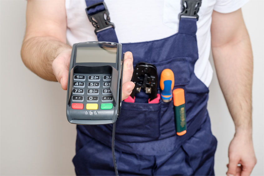 Man with tools holding bank payment terminal. Salary concept